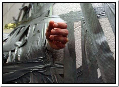 Picture of a hand duct taped to a wall.