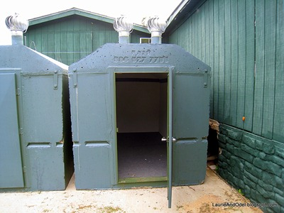Solid concrete tornado shelter has a heavy metal door.