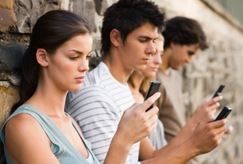 Closeup of young men and women holding cellphone