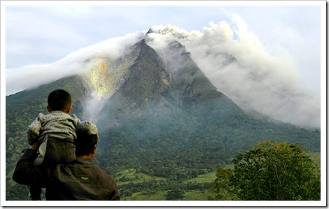 A man and his son look as the Sinabung volcano spews thick smoke in Karo district in North Sumatra