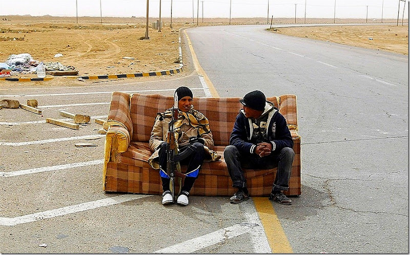 Rebel fighters sit on a sofa at a check point in Ajdabiyah, March 15, 2011. (GORAN TOMASEVIC, Reuters)