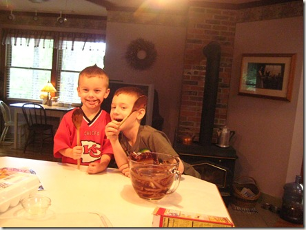 Austin and Dakota grinning as they eat the brownie batter