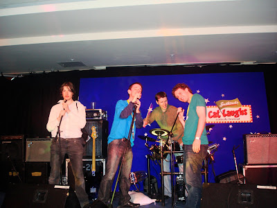 4 people on a stage singing at microphones and posing like ponces - three of them are me, Anthony McG and Darren Byrne