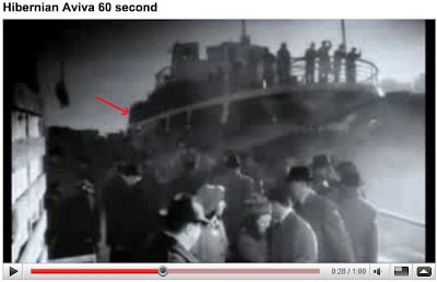 screenshot from Hibernian YouTube video showing Emigrant boat with red arrow pointing at indistinct figure towards the boat rear