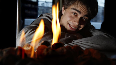 image shows Rybak sitting with his head resting on his arms, with the flames of a fire in the foreground