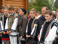 Anca Boagiu şi Gheorghe Flutur în mijlocul copiilor îmbrăcaţi în costum popular - Mitocul Dragomirnei, Suceava