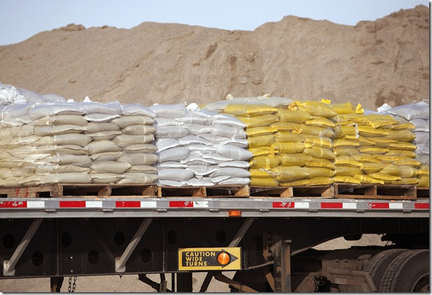 A pile of sand sits behind a truck loaded with new sandbags in the parking lot outside ÒSandbag CentralÓ in Fargo, N.D. Efforts began in Fargo Monday, Feb. 14, 2011, to fill 3 million sandbags by mid-March in anticipation of the areaÕs third consecutive major spring flood. (MPR Photo/Ann Arbor Miller)