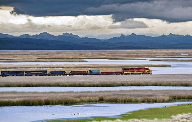 Train passes beside a beautiful landscape beside the Andes Mountain during the Southern Hemisphere summer.