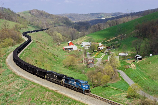 A weathered ExConrail Dash-8 train fills the quiet green valley the Manor Branch at Time in Pennsylvania
