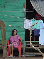 Date: January 2004</p> <p>Location: Roatan Island, Honduras</p> <p>Old lady sitting outside her daughter's house.  The daughter is inside the house.  Her mother (?) is sitting outside, obviously not in a ggod state.  There is a barbed wire fence in front of her.  Vivid colours.