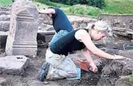 Susan Buckland crawls into a ditch in the name of archaeology at a Roman fort on Hadrian's Wall