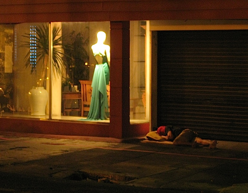 homeless person sleeping in front of a fashion designer's atelier