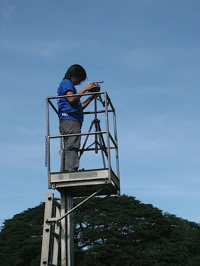recording an event from a small platform attached to the top of a ladder