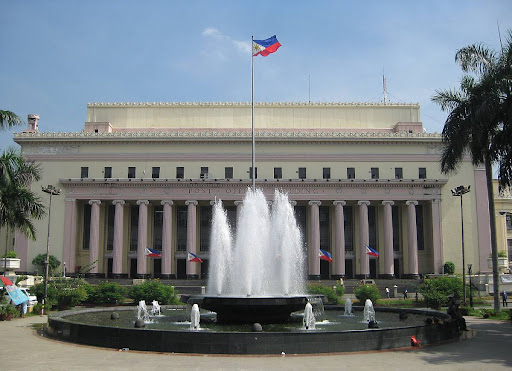 full facade of the Manila Central Post Office building with the fountain of Liwasang Bonifacio