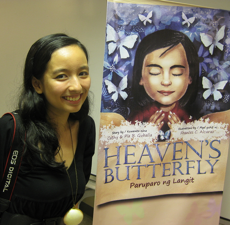 Pia Guballa with a banner of her book 'Heaven's Butterfly'