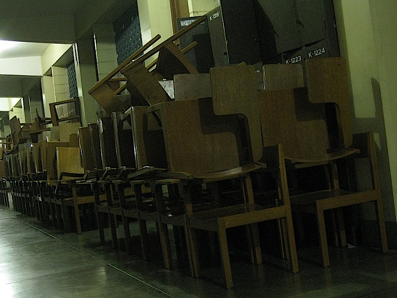 stacks of school chairs outside a classroom