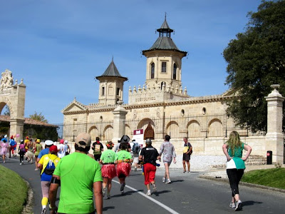 Runners in front of a chateau during the Medoc Marathon