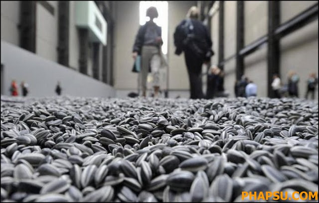 Visitors walk through the art installation 'Sunflower Seeds' by Chinese artist Ai Weiwei  in London, Monday, Oct. 11, 2010. The specially commissioned art piece takes the form of a field of sunflower seeds inside the Turbine Hall at Tate Modern gallery,  made of over 100 million handmade unique porcelain replicas of sunflower seeds, made by Chinese Artist Ai Weiwei, and will run until May 2, 2011. (AP Photo/Lennart Preiss)