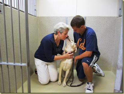 Judi and James in the kennel with Reyna.  Reyna is giving Judi a kiss on her face.