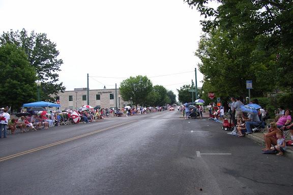 美国人民的兴致很高啊——虽然天空雨丝不断,大家伙儿还是早早地在游行队伍经过的街道两旁等候了;基本上全家出动,户外活动用的座椅、帐篷都搬出来了……
