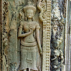 This Thommanon Devata (sacred female image) in pleated sampot is particularly slender and her stomach is unmarked. She displays the devata mudra over her heart and by her side. Note that the toe of her right foot rests on the inner ankle of her left foot, a characteristic pose of many devata. Siem Reap, Cambodia http://www.Devata.org