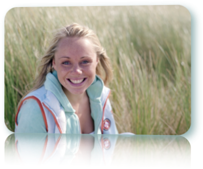 Blond woman smiling in a grassy field.