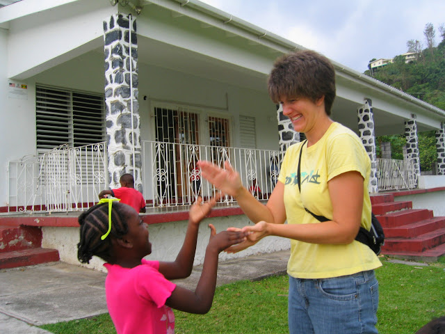 Michelle plays a clapping game with a Grenadian girl in front of the orphanage.