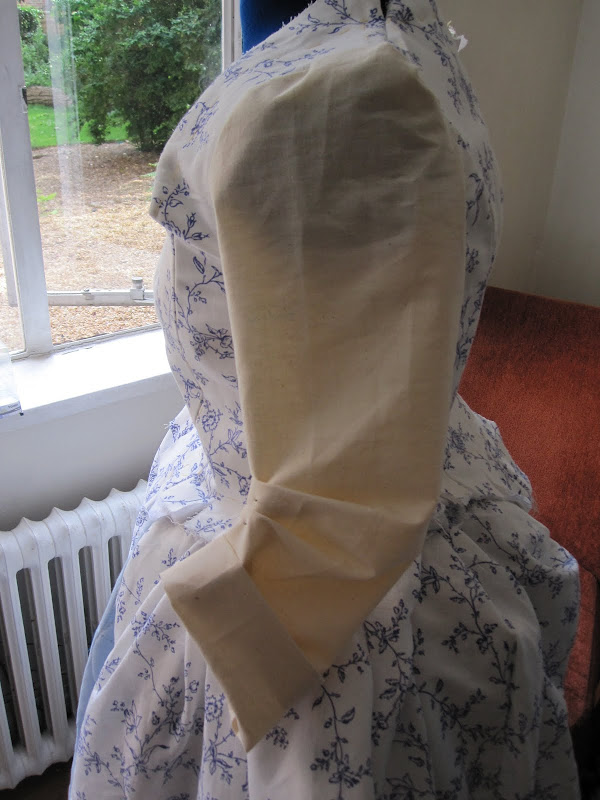 Sleeve pined to make a bend at the elbow and folded back to make a cuff
