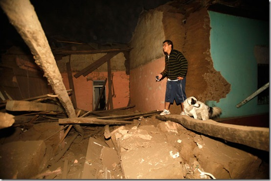 A resident of Talca, Chile, walks amid debris of a destroyed house after a powerful earthquake struck the country early Saturday, Feb. 27, 2010. (AP Photo/Roberto Candia)