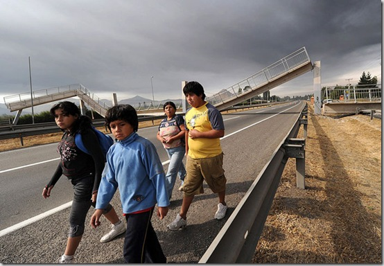 People walk along a highway with a collapsed bridge in the background in the outskirts of Santiago after a huge 8.8-magnitude earthquake rocked Chile early killing at least 78 people, on February 27, 2010. The massive quake plunged much of the Chilean capital, Santiago, into darkness as it snapped power lines and severed communications, and AFP journalists spoke of walls and masonry collapsing. People in pyjamas fled onto the streets. AFP PHOTO/MARTIN BERNETTI (Photo credit should read MARTIN BERNETTI/AFP/Getty Images)