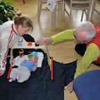 Farfar underholder Silje med hendes nye legetøj
