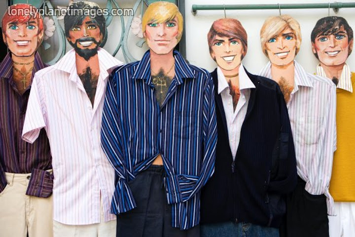 six hairy chested mannequins with different hair colors in a shop window
