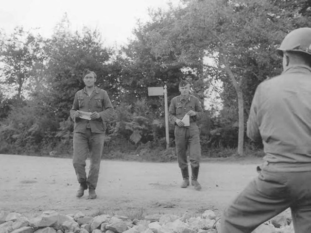 "German soldiers surrender in Brittany, France, in 1944, carrying the ""safe conduct"" passes dropped in an Allied psychological warfare campaign."
