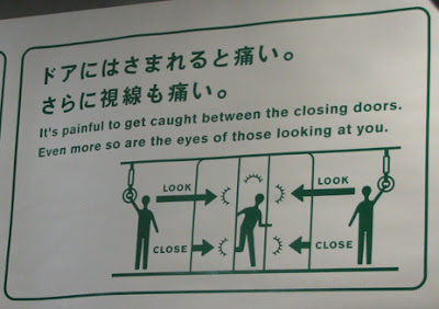 Photo of a sign in a Japanese train: It's painful to get caught between the closing doors. Even more so are the eyes of those looking at you.