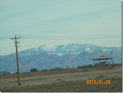 snow on the mountains past Coolidge with the Casa Grande Ruins in the foreground