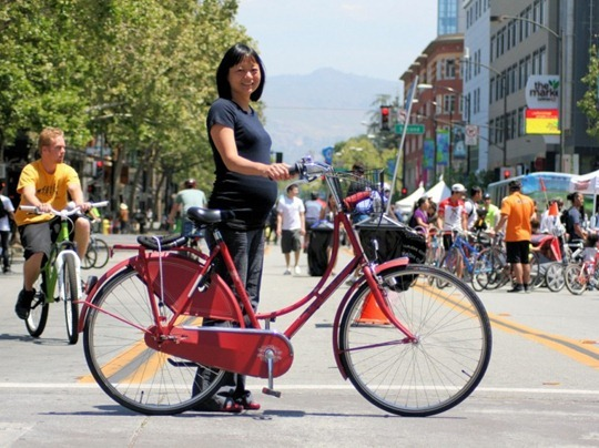 Pregnant woman with red Dutch bike in California