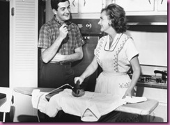 woman ironing in kitchen with hubby