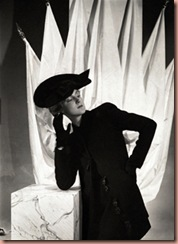Model, leaning on a square pedestal with white drapery hanging from poles behind her, wearing a dark wool, long jacketed suit with large, figurine buttons, by Schiaparelli, and a black Merry Widow felt hat, inspired by the costumes of Mae West's new film