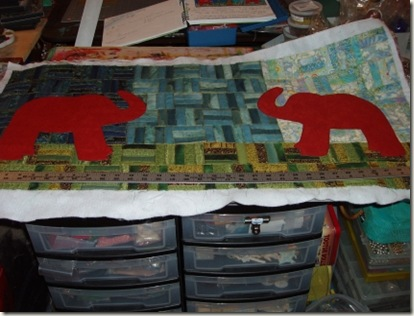 11 elephants pinned to quilt background