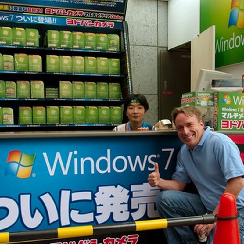 Linus Torvald poses in front of Windows 7 stall