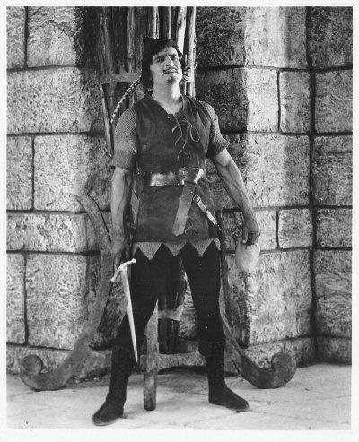 Fairbanks: Robin Hood standing by wall with sword
