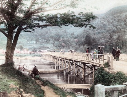 Togetsukyo bridge in Arashiyama, Kyoto, Japan. Horinji Temple can be seen on the hillside. Women in kimono stand on the bridge, a man is fishing under a cherry tree. A boat passes under the bridge. The bridge was destroyed by a flood in 1892. Late 19th century albumen photograph by Tamamura Kozaburo (1856-19??).