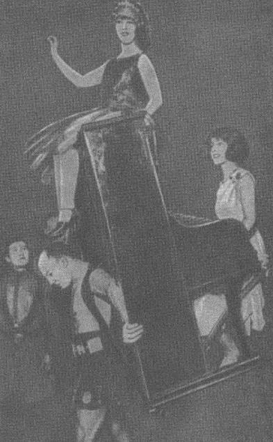 Александр Засс несет пианино с пианисткой и танцовщицей