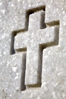 Cross carved into a veteran's headstone. Memorial to fallen soldier carved into granite