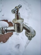 frozen faucet with the ice and snow in background