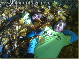 #4 of 5 (right) with a friend in a pile of leaves they raked up