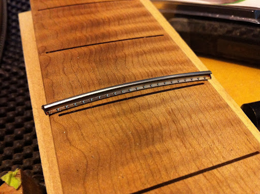 Note that the fret slots do not extend all the way to the edges of the fretboard! This board was radiused (16&amp;quot; to 20&amp;quot; compound radius) and slotted on a CNC for hyper-accurate fret placement. Stopping the fret slots short of the edges of the board gives a &amp;quot;bound&amp;quot; look without binding, and makes the board stiffer overall, since it has 3 mm &amp;quot;rails&amp;quot; down each side. Normally a slotted board wants to curl up, since you're essentially cutting kerfs into the piece of wood. The slots themselves are also radiused to match the board, so there's no waste of material there either.
