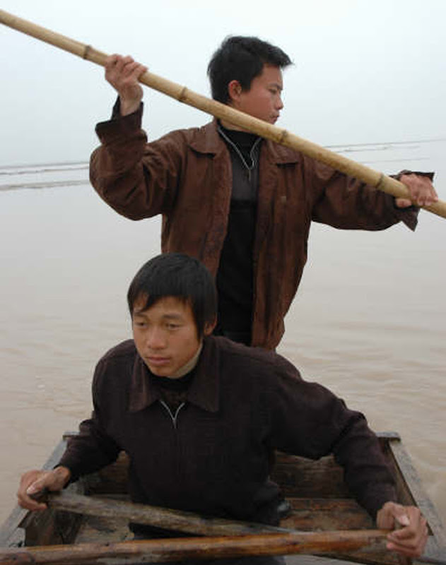 A scene from He Jianjun's portrait of two young Chinese fisherman, RIVER PEOPLE