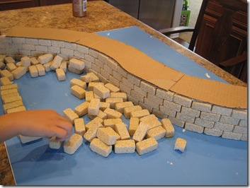 step 4 put another layer of bricks on top of the floor cardboard layer and build up castle on both ends of wall