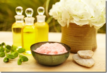 Pink exfoliation salt scrub at spa with flower and massage oil